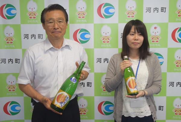 日本酒「かわち丸」を手にする雑賀正光町長㊧(河内町役場で)