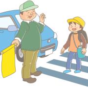 横断歩道を渡る子供と黄色い旗を持って見守るおじさん