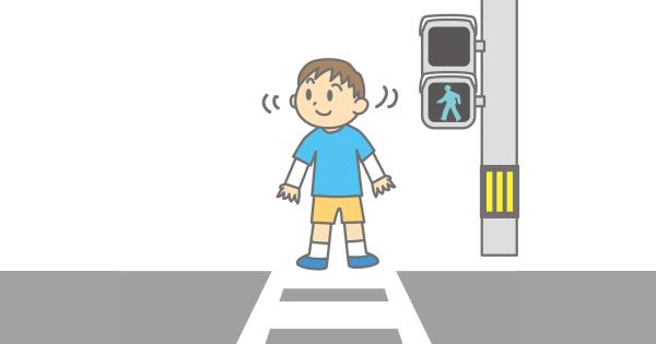 横断歩道で安全を確認している男の子