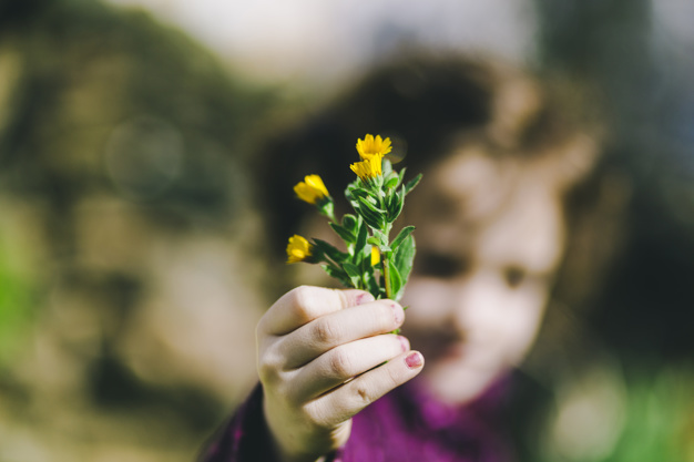 blurred-girl-showing-wild-flowers_23-2147830678.jpg