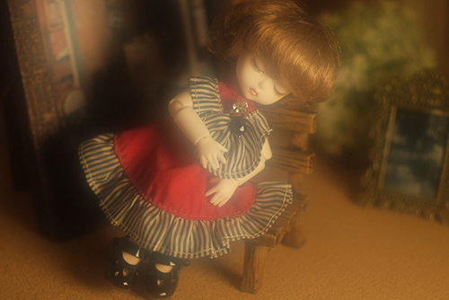 DOLL FACTORY・Baby Ariの小さな眠り目の子、Emma(エマ)。赤いドレスで、ベンチに座り、どこかおすまし顔。