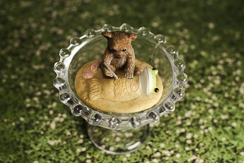 ツバキアキラが撮ったカエルのコポー。ガラスの器の上で、クマくんにデコレーションされているコポタロウ。