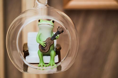 ツバキアキラが撮ったカエルのコポー。宙に浮いたガラス玉の中でウクレレを弾くコポタロウ。